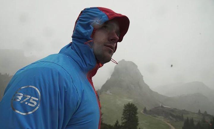 Mann in Regenjacke in den Bergen